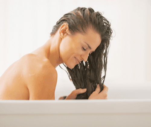 Woman washing her hair in the bathtub.