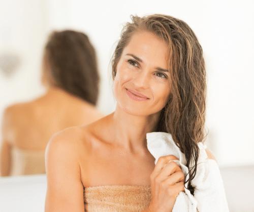 Woman towel drying her damp hair.